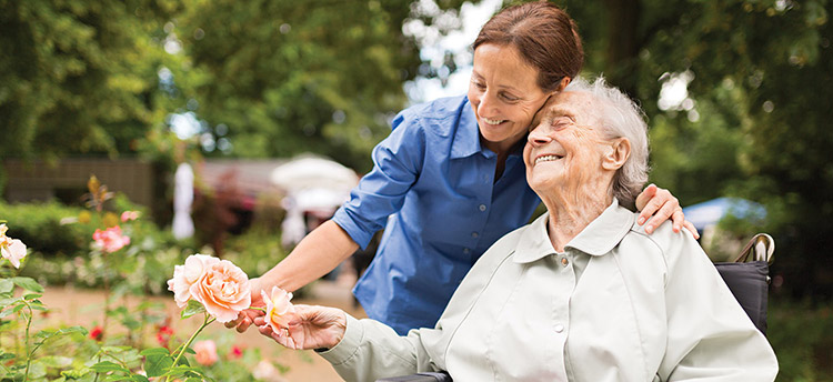 A happy senior woman and her caregiver looking at flowers